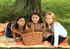 Girls on blanket with basket Stock Photo