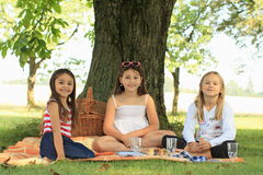Girls on blanket having picnic Stock Photos