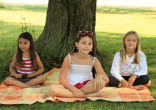 Girls on blanket. Three girls sitting on blanket under the tree Royalty Free Stock Images
