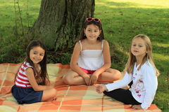 Girls on blanket. Three girls sitting on blanket under the tree Stock Images