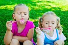 Girls blowing bubbles Stock Photos