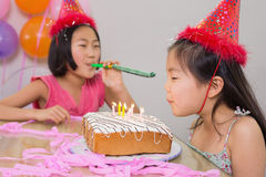 Girls blowing noisemaker and birthday candles Royalty Free Stock Image