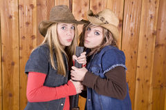 Girls blowing on shotgun barrel Stock Photos