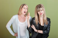 Girls Blows Off Frustrated Mom. Rude retro-styled daughter gestures angry mom to be silent Royalty Free Stock Image