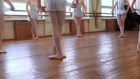 Girls in blue ballet suits stand in third position and begin dancing in circle on floor of frayed ballet classroom. HD. Girls in blue leotard stand in third stock video