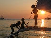 Girls on boat. Silhouetted against setting sun Stock Photo