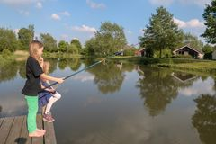 2 Girls are at a boat bridge at a lake are fishing royalty free stock image