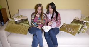 Girls with Bowl of Popcorn Watching Movie at Home. Two Young Women in Winter Clothes Having a Bowl of Popcorn While Watching Movie at the Living Room Inside the stock footage