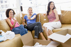 Girls with boxes in new home. Three girl friends relaxing with champagne by boxes in new home Stock Photo
