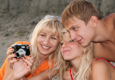 Girls and boy with camera on a beach Stock Photo