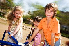 Girls and boy on carousel Royalty Free Stock Images