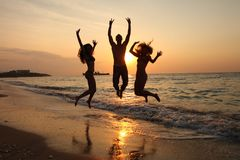 Girls and Boy DANCING IN SUNSET ON SEA Stock Photo