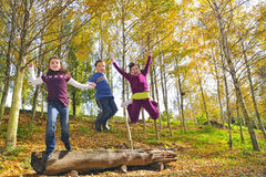 Girls and boy jumping. In nature in autumn time Stock Images
