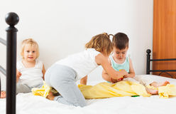 Girls and a boy playing on   bed. Stock Photo