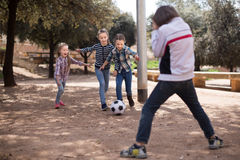 Girls and a boy playing soccer in the park in autumn Royalty Free Stock Image