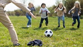 Girls and boy playing soccer in park in autumn stock photography