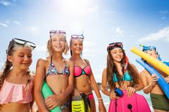 Girls and boy portrait in bikini with scuba masks. Stand over sky on sunny hot day on the beach Royalty Free Stock Photo