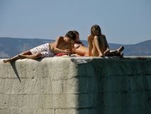 Girls and boy on sea port. Boy and girl talking on holiday in Croatia Royalty Free Stock Image