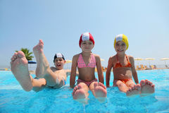 Girls and boy sit on skirting in pool. Two girls sit on skirting in  pool and feet overwater and boy lift which falls in water, underwater package shot Stock Photography