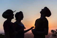 Girls Boy Talk Laugh. Girls Boy teenagers friends talk laugh silhouetted at sunset stock photos
