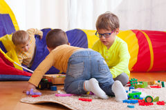 Girls and boy with toys. Two girls and boy with toys on  floor at home Stock Photography