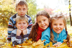 Girls and boys in autumnal park. Beautiful girls and boys lie in autumnal park stock photos