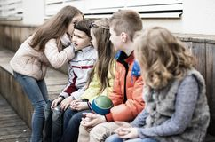 Girls and boys on bench playing games in yard royalty free stock photos