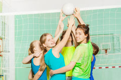 Girls and boys playing volleyball in gymnasium Royalty Free Stock Image