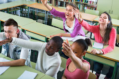 Girls and boys raising their hands in the class Royalty Free Stock Photos
