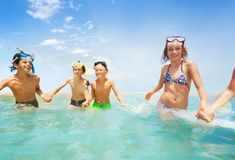 Girls and boys running in shallow water together Royalty Free Stock Images