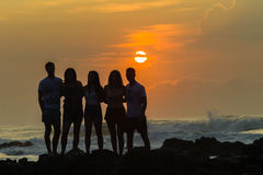 Girls Boys Silhouetted Beach Sunrise Ocean Stock Photo