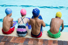 Girls and boys sitting at poolside Stock Photo