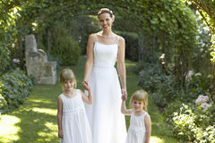 Girls And Bride Standing Under Ivy Arches Stock Photo