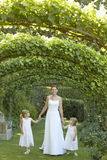 Girls And Bride Walking Under Ivy Arches Stock Images