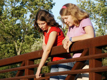 Girls on bridge. Looking at object below Royalty Free Stock Image