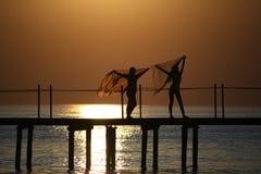 Girls on a bridge at sunset. Royalty Free Stock Image