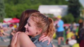 Girls with Britain flag on cheeks watch football match in fan zone. Side view. Girls with Britain flag on cheeks watch football match stock footage