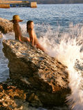 Girls and broken waves. Girls sitting on a rock and watching the waves breaking Royalty Free Stock Photo