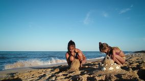 Girls are building a sand castle. Girls play on the seashore stock footage