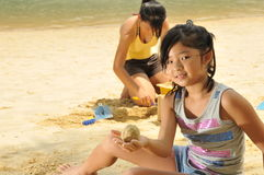 Girls Building Sandcastle By The Beach Royalty Free Stock Photo