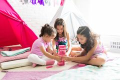 Girls Building Tower Of Blocks During Slumber Party. Multiethnic girls building tower of blocks during slumber party at home stock photo