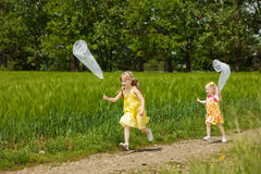 Girls with butterfly net having fun Royalty Free Stock Photo