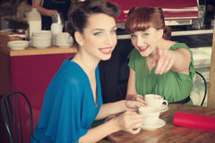 Girls in cafe. Two beautiful girls in retro style in retro cafe Stock Image
