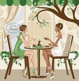 Girls at the cafe. A black woman in white outfit and a white woman in green are sitting at a cafe, having a coffee Stock Images