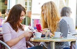 Girls in a cafe with handy Royalty Free Stock Photos