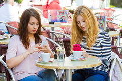 Girls in a cafe with handy Royalty Free Stock Image