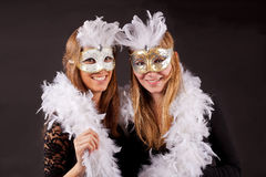 Girls carnaval mask and feathers. Two blond girls with carnaval masks with feathers stock photography