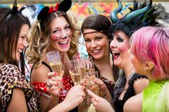 Girls at Carnival parade clinking glasses with champagne. Happy girls at Carnival parade clinking glasses with champagne Royalty Free Stock Photography