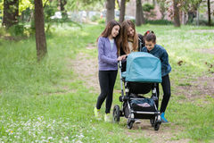 Girls carrying a pram Stock Image