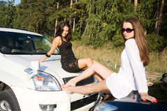 Girls with cars. Two girls with two cars resting on the road Royalty Free Stock Image